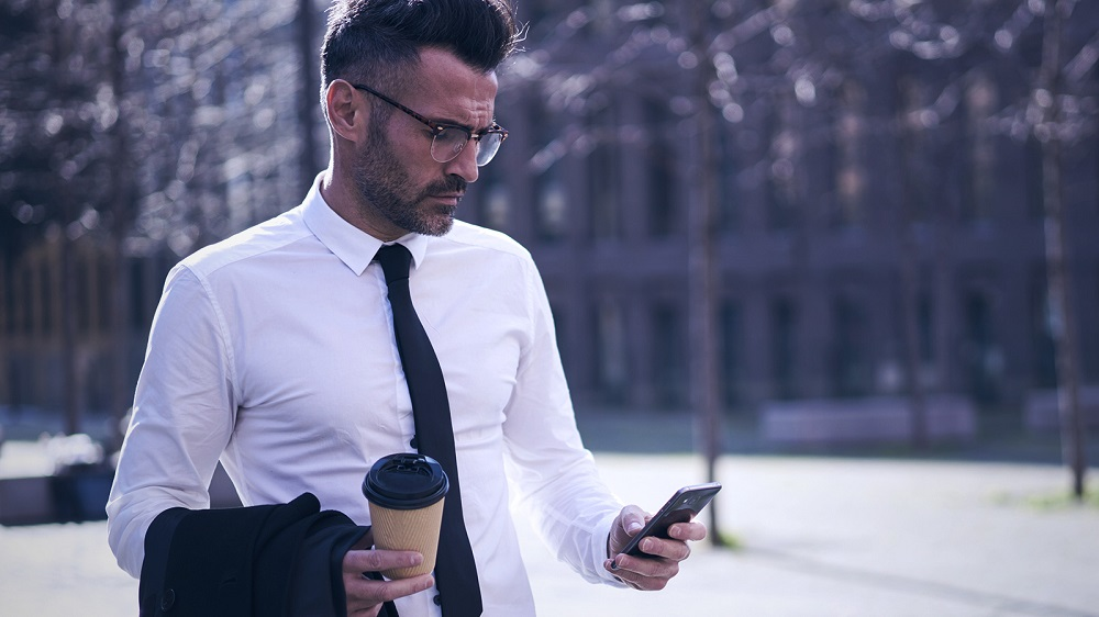 Suited man holding coffee and looking at his smartphone
